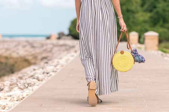 woman wearing black and white striped maxi skirt holding brown bag